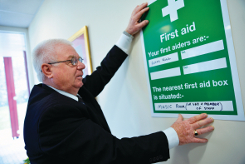 An image of first aid poster with Health & Safety representative putting it up
